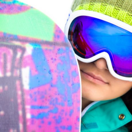 young woman in sport sunglasses with a snowboard. close-up